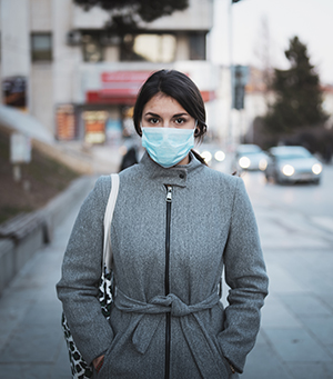 Woman outdoors in cityscape wearing a face mask